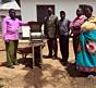 Vodilni člani zadruge Usongwe in naprava za ročno čiščenje kavnih češenj